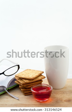 Cracker and coffee or tea with a book on white background - stock photo