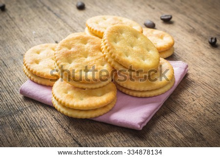 Cracker stack together on wooden background. - stock photo