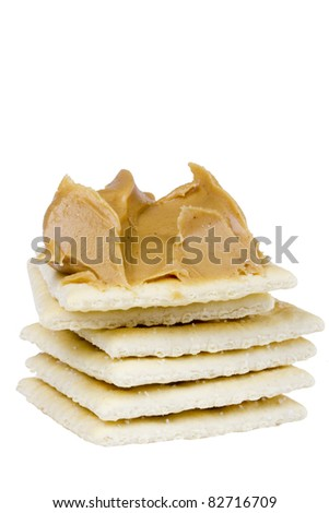 Cracker with peanut butter laying on a stack of crackers on a white background. - stock photo