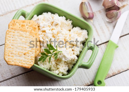 Crackers and cottage cheese with garlic on wooden background. Rustic style. Bio/organic/natural ingredients. Healthy eating.