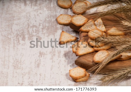 Crackers and wheat ears on the wooden background
