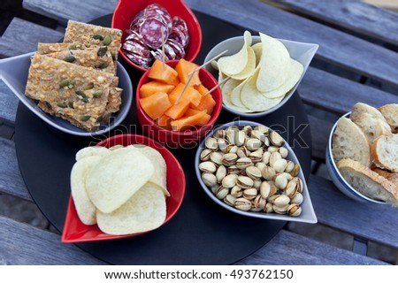 Crackers, chips, melon and sausage on a table