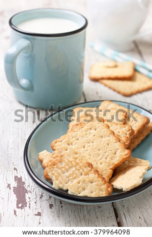 crackers on a blue plate and a mug of milk on a white wooden background - stock photo
