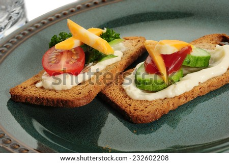 Crackers served on plate with cucumber, tomato and cheese - stock photo