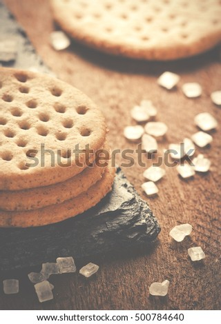 Crackers stack together on black stone, coarse sugar on wooden background.