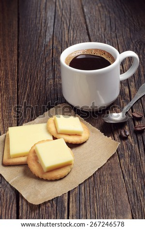 Crackers with cheese and cup of hot coffee on rustic wooden table