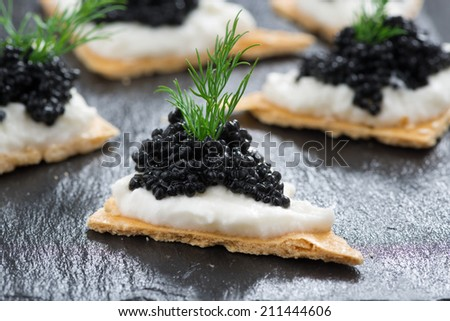 crackers with cream cheese and black caviar, horizontal