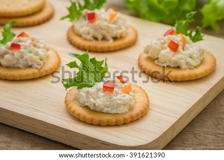 Crackers with tuna salad on wooden plate   - stock photo