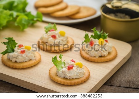 Crackers with tuna salad on wooden plate and tuna spread in canned