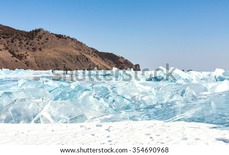 Cracks and ice blue ice on the surface of Lake Baikal. Frozen lake under a blue sky in winter. Mountains and hills with pine trees. Siberia, Russia. Horizon. Winter. - stock photo