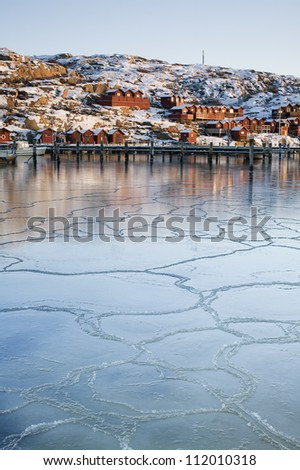 Cracks in ice on the river with town in the background, panoramic view