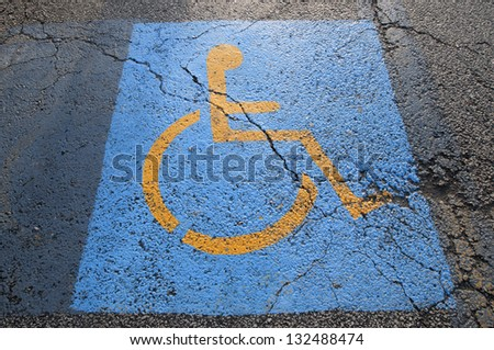 Cracks in parking lot pavement on handicapped parking spot  signifying failing infrastructure