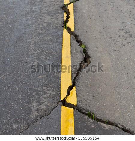 Cracks on asphalt the yellow line dividing lanes with grass  - stock photo
