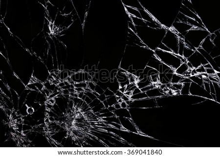 Cracks on the glass against black background - stock photo