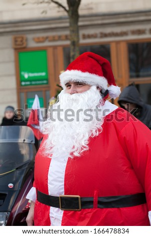 CRACOW, POLAND - DECEMBER 8, 2013: the parade of Santa Clauses on motorcycles around the Main Market Square in Cracow