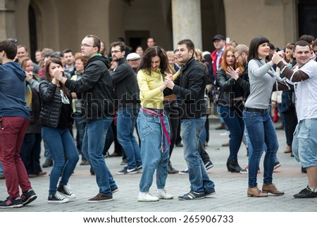 CRACOW, POLAND - MARCH 28, 2015:  the international Flashmob day of rueda de Casino,57 countries , 160 cities. Several hundred persons dance Hispanic rhythms on the Main Square in Cracow