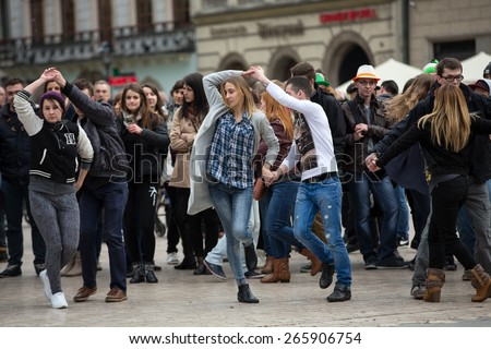 CRACOW, POLAND - MARCH 28, 2015:  the international Flashmob day of rueda de Casino,57 countries , 160 cities. Several hundred persons dance Hispanic rhythms on the Main Square in Cracow  - stock photo