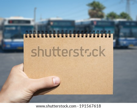 craft horizontal blank notebook in man hand and bus station background - stock photo
