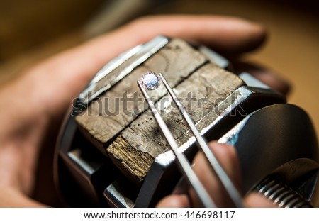 Craft jewelery making with professional tools. Ring repairing. Putting the diamond on the ring. Macro shot.  A handmade jeweler process, manufacture of jewelery.