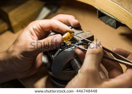 Craft jewelery making with professional tools. Ring repairing. Putting the diamond on the ring. Macro shot.  A handmade jeweler process, manufacture of jewellery. - stock photo