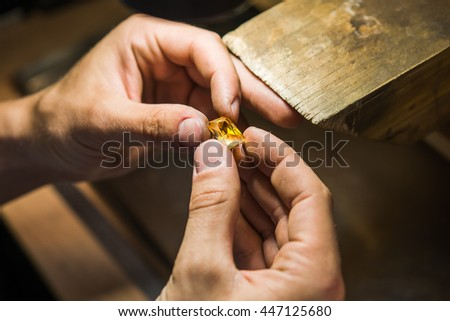 Craft jewelery making with professional tools. Ring repairing. Putting the diamond on the ring. Macro shot.  A handmade jeweler process, manufacture of jewelery. - stock photo