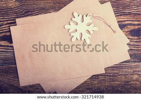 Craft paper blank card for holiday message on wooden background viewed from above - stock photo