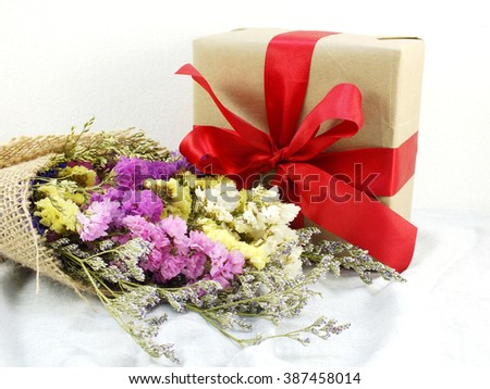 craft paper gift box with ribbon bow and statice flower bouquet with fabric texture