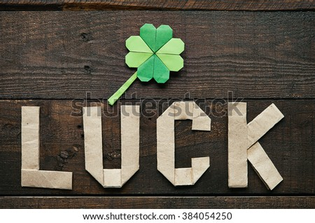 Craft paper origami LUCK lettering on dark barn wood rustic background. Green clover leaf. St. Patrick's Day greeting postcard template. - stock photo
