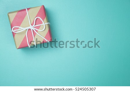 Craft paper wrapped present box craft rope bow ribbon on blue background, top view