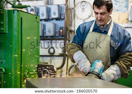Crafts Man Worker grinding Metal Product at Factory Workshop - stock photo
