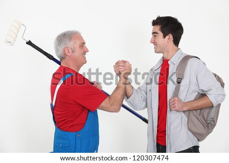 craftsman and apprentice shaking hands - stock photo