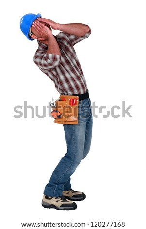 craftsman covering his face with his hands - stock photo