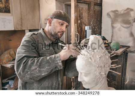 Craftsman creating shape of sculpture in his workshop