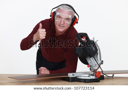 craftsman cutting a board with an electric saw - stock photo