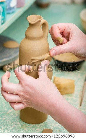 Craftsman decorating bottle made of fresh clay in pottery workshop. Shallow depth of field. Focus on bottle and fingertips. - stock photo