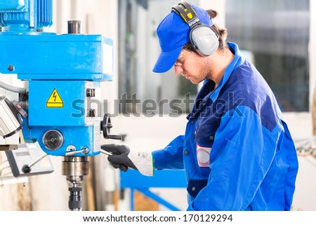 Craftsman drilling metal with drill in workshop - stock photo