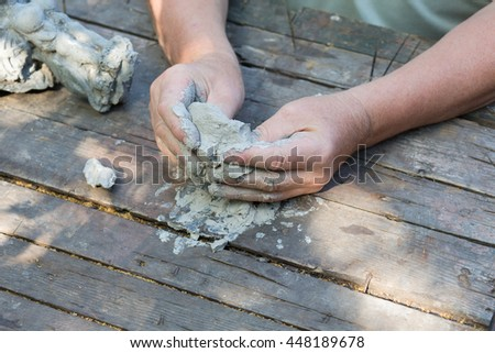 Craftsman hands working with clay, closeup, old wooden table, top view.