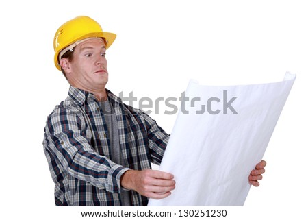 craftsman holding a blueprint and looking very surprised - stock photo