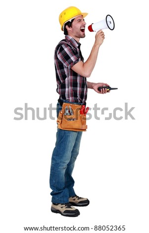 craftsman holding a walkie talkie and shouting through a megaphone - stock photo