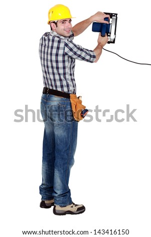 craftsman holding an electric saw - stock photo