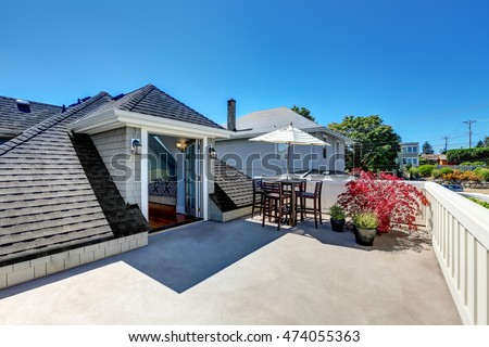 Craftsman house roof top terrace with living area with plant pots. Table set with umbrella. View of attic bedroom. Northwest, USA