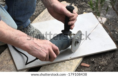 Craftsman is cutting a floor tile with a portable angle grinder - stock photo