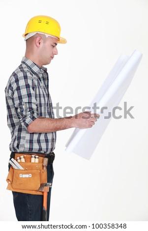 craftsman looking at a blueprint - stock photo