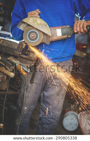 Craftsman sawing metal with disk grinder in workshop. Shallow depth of field.