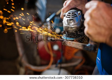 Craftsman sawing metal with disk grinder in workshop. Very shallow depth of field. Focus is only on few sparkles. - stock photo