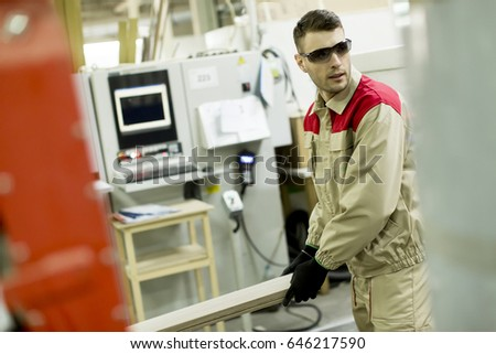 Craftsman wearing working clothes and protective eyewear woodworking in furniture industry operating on machine