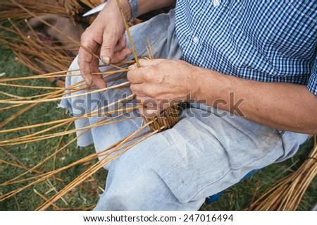 craftsman weaving a wicker basket - stock photo