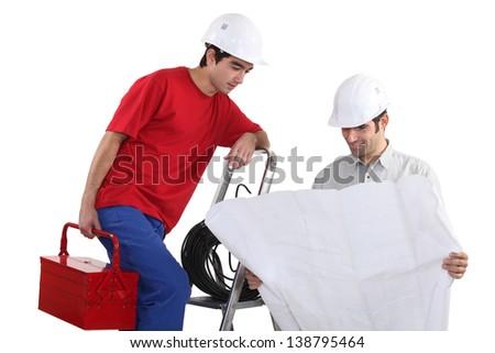 craftsmen looking at a blueprint - stock photo