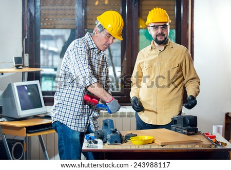 Craftsmen use an electric drill, selective focus