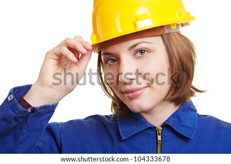 Craftswoman in overall putting on yellow safety helmet - stock photo